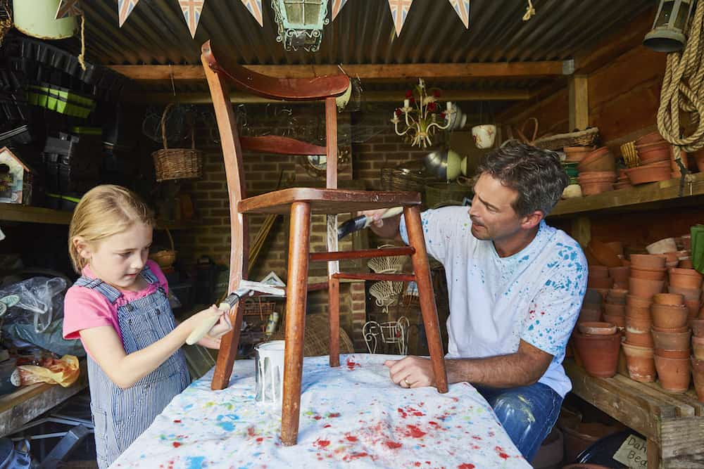Father and daughter painting chair in workshop