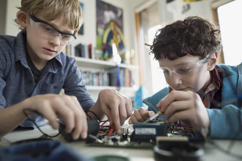 Focused boys assembling circuit board