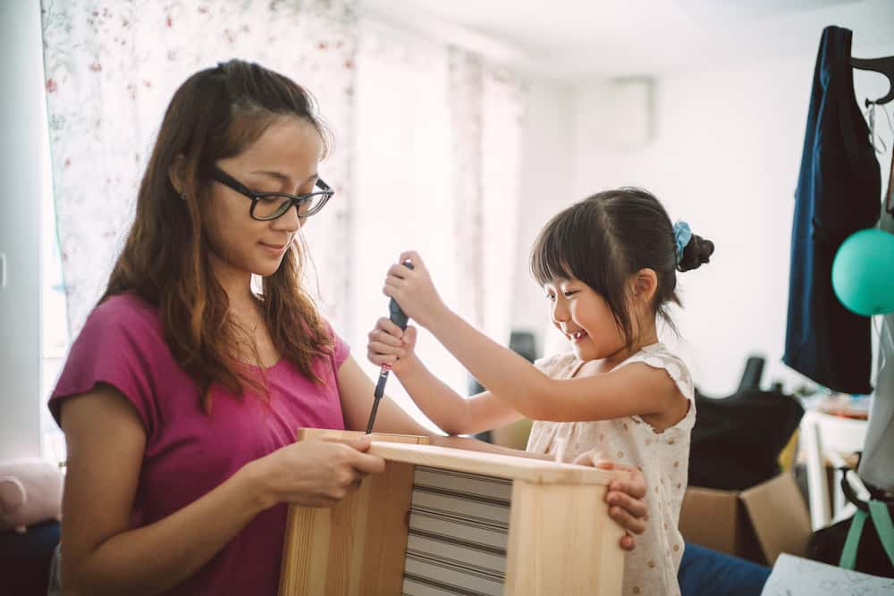 Pretty young mom assembling furnitures with lovely little daughter joyfully