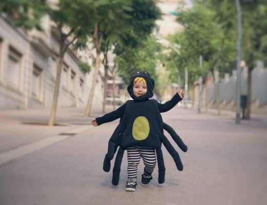 Happy baby boy running dressed as a spider